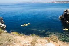 Paddleboarding grupp i den Baleal fjärden, Peniche, Portugal konkurrensar som dyker pölsportar som simmar vatten Arkivbild