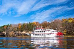 Paddleboat, st.croix river. A paddleboat, travels up along the sandstone cliff shoreline, of the st. croix river, wisconsin Stock Image