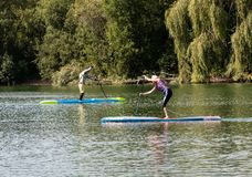 Paddleborading sur le braillement de lac photo libre de droits