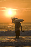 Paddler con surfski en hombro en la salida del sol Imagen de archivo