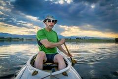 Paddler de canoë sur le lac au susnset Photographie stock libre de droits