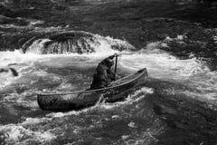 Paddler féminin dans un canoë de whitewater Image stock