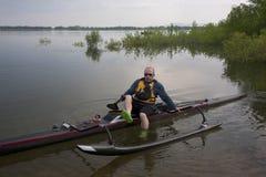 Paddler maturo nella corsa della canoa di intelaiatura di base della gru Fotografia Stock