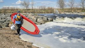 Paddler portaging paddleboard over river rapid. Senior paddler is portaging inflatable stand up paddleboard over a rapid - South Platte River in early spring royalty free stock photos