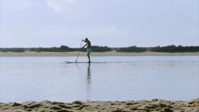 Paddler silhouette at Fuseta, in Ria Formosa wetlands landscape, Algarve, southern Portugal. stock video