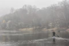 Paddler solitaire sur une rivière brumeuse Photo stock