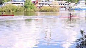 Paddlers naviguant sur des bateaux de sports sur la rivière près de grands bateaux banque de vidéos