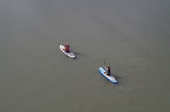 Paddlers on the River. Two stand up paddlers getting ready to paddle on the river Royalty Free Stock Images