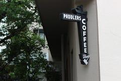 Paddlerscoffee shop undertecknar in staden arkivbild