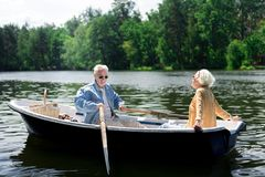 Happy elderly man holding paddles while sitting in boat with wife. Paddles and boat. Happy elderly men holding paddles while sitting in boat with his appealing royalty free stock images