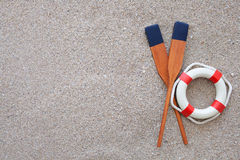 Paddles and life buoy lying on a sand Royalty Free Stock Images
