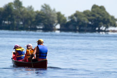Paddling. A father and his two daughter's out for a paddle in a canoe on the lake royalty free stock photo