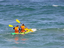 Paddling. Two canoeist paddling off shore royalty free stock images