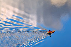 Paddling on a calm lake. A person paddling in a canoe on a calm lake, with clouds and blue skies reflecting on the surface of water Stock Photography