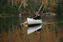 Paddling a Canoe on an Autumn Lake Stock Image