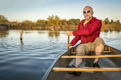 Paddling canoe on calm lake. Senior paddler enjoying paddling a canoe on a calm lake, Riverbend Ponds Natural Area, Fort Collins, Colorado royalty free stock photography