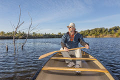 Paddling canoe on a lake Royalty Free Stock Photos
