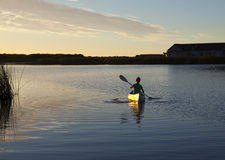 Paddling canoe at sunset. A person paddling a canoe away from shore on a quiet lake at sunset Stock Images