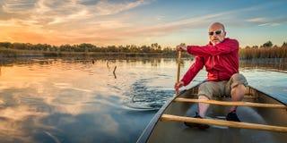 Paddling canoe at sunset Royalty Free Stock Image