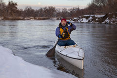 Paddling canoe on a winter river Stock Photography