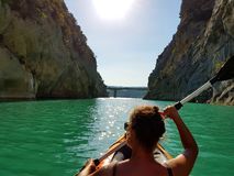 Paddling in Crystal clear turquoise water in Gorges du Verdon, Provence Alps, France. A kaukasian Sun-tanned female Paddling in an inflatable kayak on Crystal Royalty Free Stock Images
