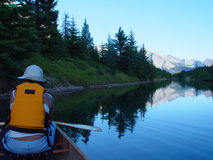 Paddling at dusk on a mountain lake. Canoing at sunset on a Canadian Rockies Royalty Free Stock Image