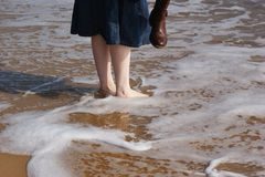 Paddling Feet. A woman on the beach paddling in the sea Royalty Free Stock Image