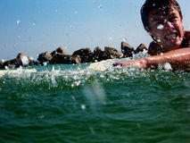 Paddling Hard. A candid shot of a teenager paddling out on his surfboard.  Water droplets litter the frame.  Jagged rocks are depicted in the background Royalty Free Stock Image