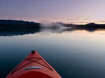 Paddling in a kayak through calm sunset waters Stock Images