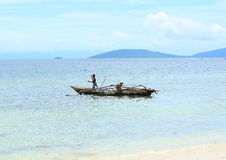 Paddling Kid. Papuan boy paddling a traditional motored boat with traditional fish spear in a shallow tropical sea water, Saporkren Village, Waigeo Island, Raja Stock Photos