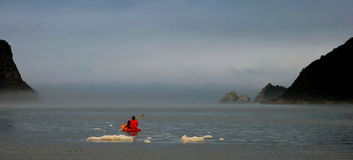 Paddling into the mist. A lone paddler moves through the early morning mist, through the gap Stock Photography
