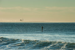 Paddling out with power plant in background. Stand up paddler taking advantage of lull between sets of waves in Ventura royalty free stock image