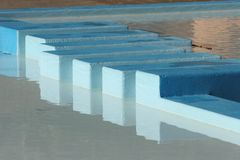 Paddling Pool reflections. Abstract lines and reflections on blue in a children's public paddling pool stock photography
