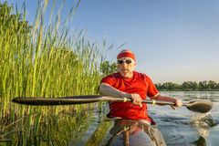 Paddling racing sea kayak on lake Stock Photography