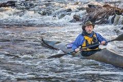 Paddling sea kayak on a river. Senior male paddling a sea kayak through river rapids at sunset Royalty Free Stock Images