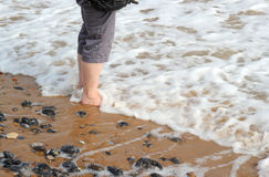 Paddling on the sea shore with bare feet. Waves breaking around a persons bare feet on the sandy beach. There is white foam in the sea and pebbles on the wet stock image