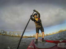 Paddling stand up board. Mature male paddler enjoying workout on stand up paddleboard (SUB), calm lake in Colorado, early spring Royalty Free Stock Photo