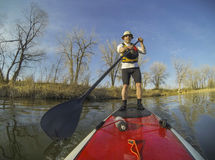 Paddling stand up board. Mature male paddler on a red stand up paddleboard (SUP), calm lake in Colorado, early spring Royalty Free Stock Photos