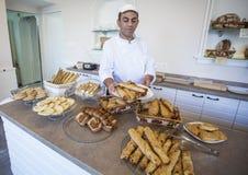 Padeiro aciganado que mostra o pão fresco, os croissant e as cookies Imagem de Stock