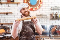 Padeiro alegre que mostra o naco de pão na cozinha foto de stock