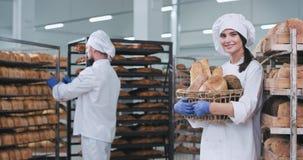 Padeiro atrativo da senhora com uma cesta grande de um pão orgânico fresco na padaria que olha em linha reta ao retrato da câmera vídeos de arquivo