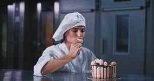 Padeiro atrativo da senhora em uma cozinha comercial da padaria depois que terminou o trabalho para tomar alguns biscoitos dos bo filme