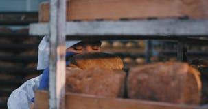 Padeiro bonito da senhora do close up na cozinha industrial da padaria veio tomar algum pão que cozido fresco cheira com video estoque