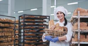 Padeiro bonito da senhora em um uniforme branco que guarda uma cesta com pão fresco e o sorriso bonito na frente da câmera filme