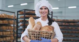 Padeiro bonito de sorriso da senhora que guarda uma cesta com pão cozido fresco em uma fábrica da padaria video estoque
