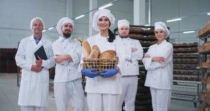 Padeiro carismático de sorriso da jovem senhora e toda a equipe principal do padeiro no meio da fabricação da padaria que olha em video estoque