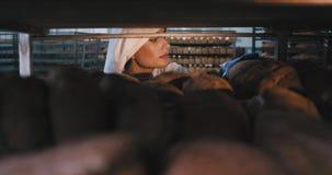 Padeiro da jovem senhora em uma indústria de padaria toma a um pão cozido fresco do prateleiras industriais e cheiro do pão com video estoque