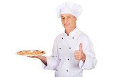 Padeiro do cozinheiro chefe com a pizza italiana que mostra o sinal aprovado Fotografia de Stock Royalty Free