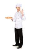 Padeiro do cozinheiro chefe com a pizza italiana que mostra o sinal perfeito Fotografia de Stock