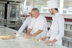 Padeiro e assistentes na cozinha da padaria foto de stock